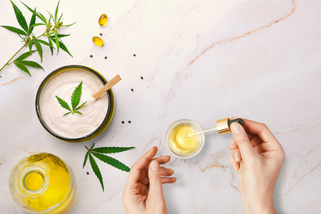 Pipette with CBD cosmetic oil in female hands on a table background with cosmetics, cream with cannabis and hemp leaves, marijuana.
